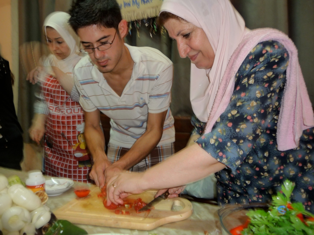 Um Ali shows a lucky student what cutting tomatoes is all about